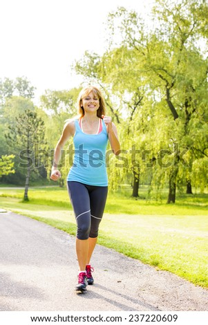 Smiling woman exercising on running path in green summer park - stock photo
