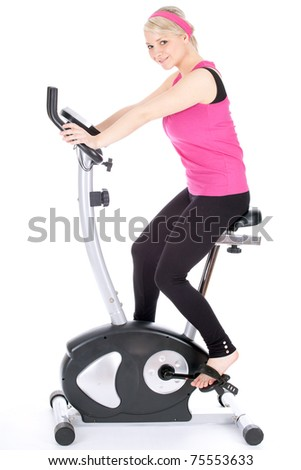 smiling woman exercising on stationary training bicycle