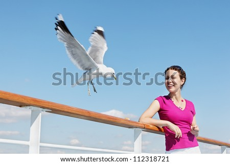 Smiling woman  feeds seagulls with bread on deck of ship. - stock photo