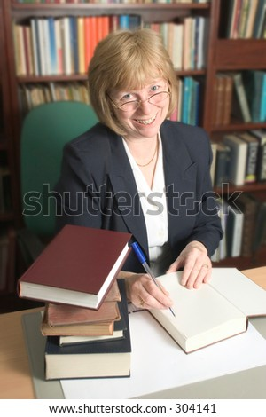Smiling woman filing the books.