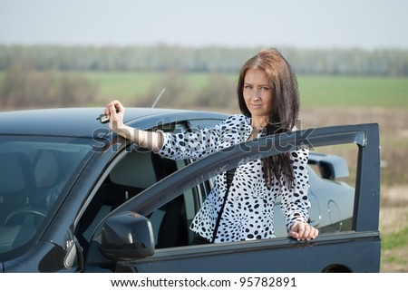 Smiling woman get in the car and looking at camera - stock photo