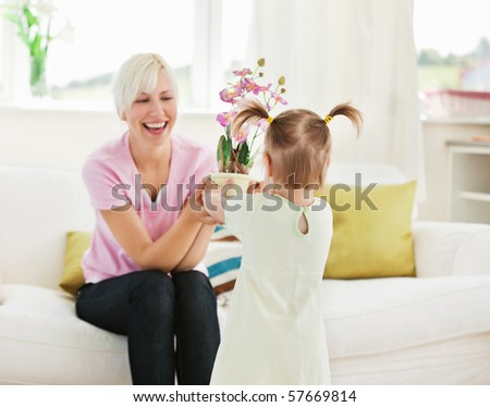 Smiling woman get surprise by her daughter in living room - stock photo