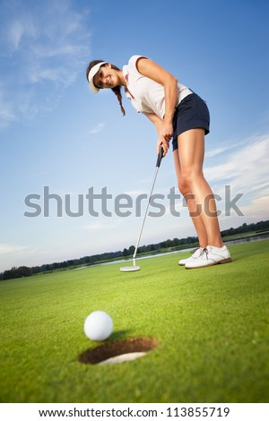 Smiling woman golf player putting successfully ball on green, ball dropping into cup, blue sky in background. - stock photo