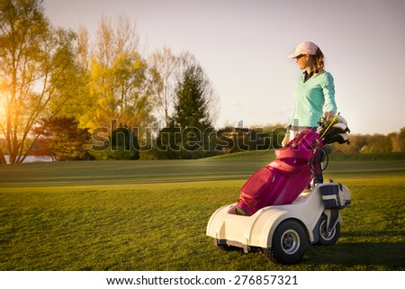 Smiling woman golf player standing at fairway at sunset with her golf bag. - stock photo