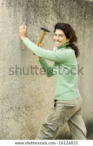 Smiling woman hammering a wall. Vertically framed photo. - stock photo