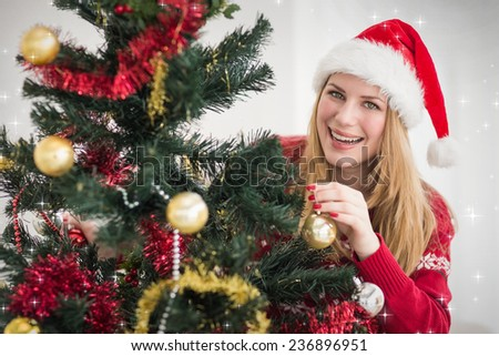 Smiling woman hanging christmas decorations on tree against snow - stock photo