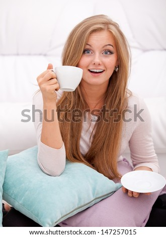 Smiling woman having an idea with white cup at home