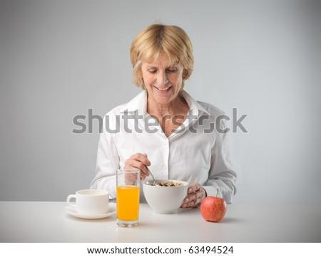 Smiling woman having breakfast - stock photo