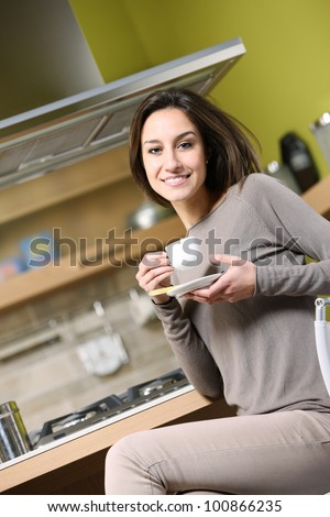 smiling woman having breakfast at home - stock photo