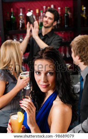 Smiling woman having drink with friends at cocktail bar - stock photo
