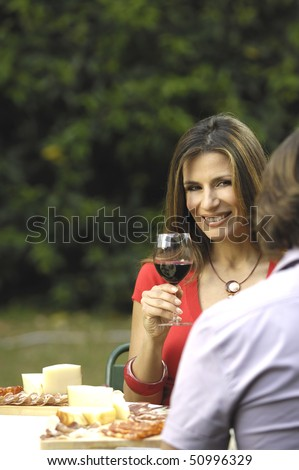 Smiling woman having meal with wine - stock photo