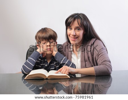 Smiling woman helping a child to read
