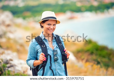 Smiling woman, hiker going on path, mountains with backpack. Concept of traveling and trekking on coastline - stock photo