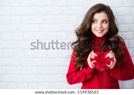 Smiling woman hold red gift box. Wall background. Concept of the New Year, Christmas and Valentine's Day.