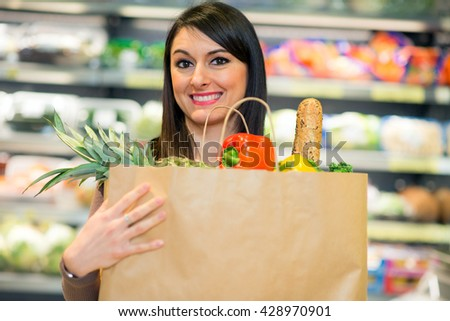 Smiling woman holding a bag full of vegetables - stock photo