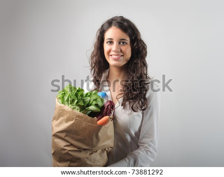 Smiling woman holding a bag with food - stock photo