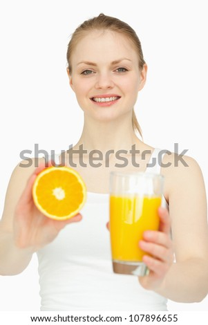 Smiling woman holding a glass while presenting an orange against white background - stock photo