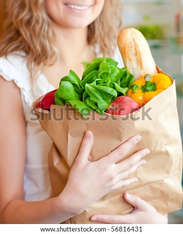 Smiling woman holding a grocery bag in the kitchen - stock photo