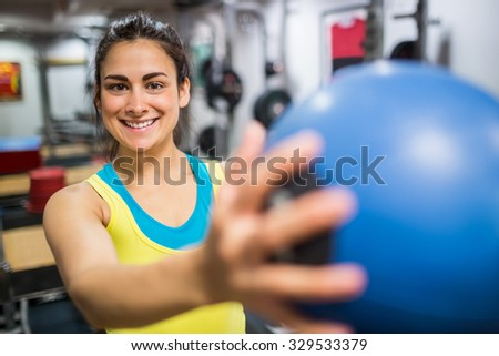 Smiling woman holding a medicine ball at the gym
