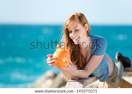 Smiling woman holding a piggy bank at the beach background