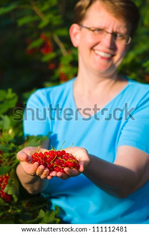 Smiling woman holding a pile of fresh red currants, focus on berries - stock photo