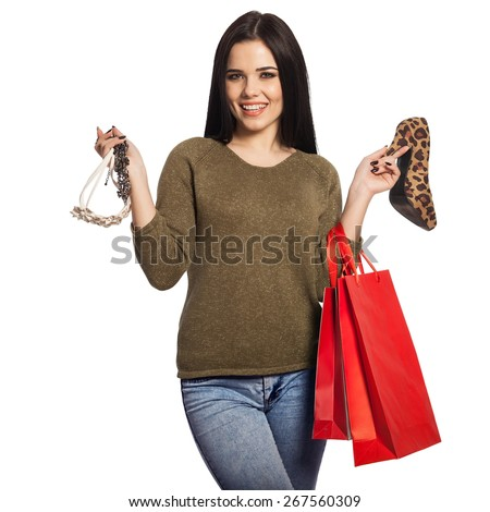 Smiling woman holding a shoe, a necklace, and red shopping bags. Gorgeous white caucasian brunette female model isolated on white background. - stock photo