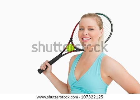 Smiling woman holding a tennis racket and ball against white background - stock photo