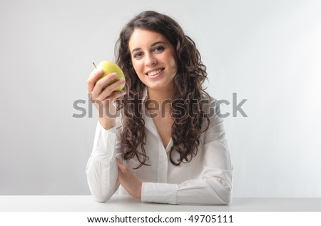 Smiling woman holding an apple - stock photo