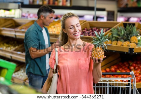 Smiling woman holding and looking a pineapple at the grocery