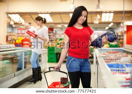 Smiling woman holding bag with mother and baby in the background - stock photo