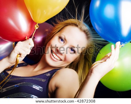 smiling woman holding ballons and celebrating - stock photo