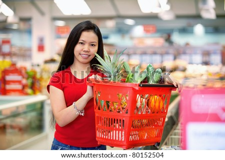 Smiling woman holding basket filled with fruits in shopping centre and looking at camera - stock photo