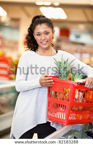 Smiling woman holding basket filled with fruits in supermarket and looking at camera