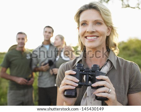 Smiling woman holding binoculars with blurred friends in background - stock photo