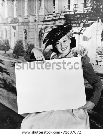 Smiling woman holding blank sign - stock photo