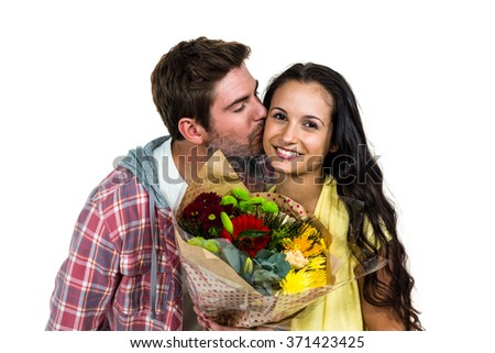 Smiling woman holding bouquet and being kissed by boyfriend on white screen - stock photo