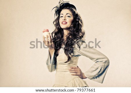 smiling woman holding cup cake isolated in studio - stock photo