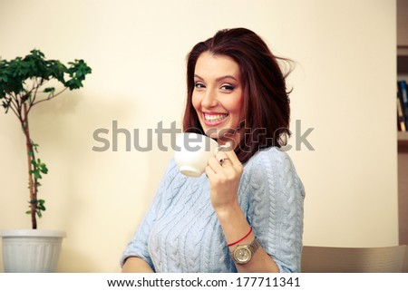 Smiling woman holding cup with coffee at home - stock photo