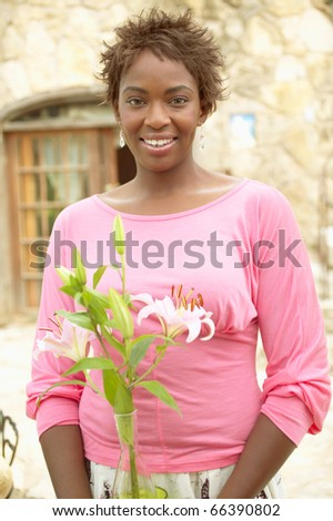 Smiling woman holding flowers - stock photo