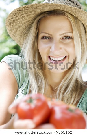 smiling woman holding fresh tomatos from her garden - stock photo
