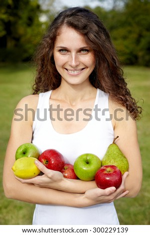 smiling woman holding fruits.Outdoor - stock photo