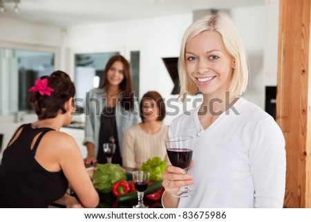Smiling woman holding glass at party with female friends in background - stock photo