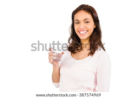 Smiling woman holding glass of water on white background - stock photo