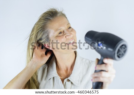 Smiling woman holding hairdryer and holding her long hair.