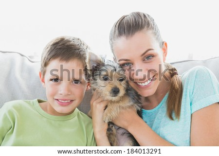 Smiling woman holding her yorkshire terrier puppy with her son at home in the living room - stock photo