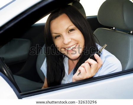 smiling woman holding key to the car - stock photo