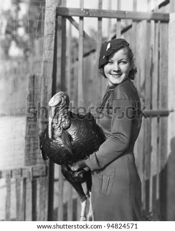 Smiling woman holding live turkey - stock photo