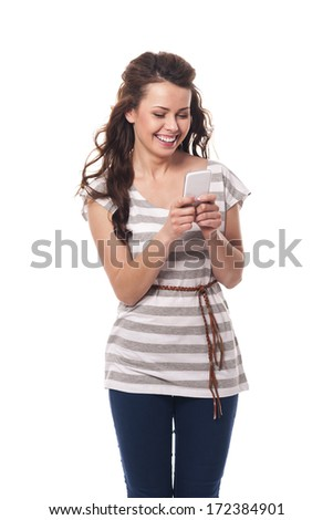 Smiling woman holding mobile phone and text messaging