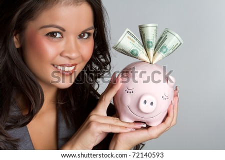 Smiling woman holding piggy bank - stock photo