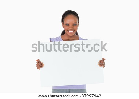 Smiling woman holding placeholder in her hands on white background - stock photo